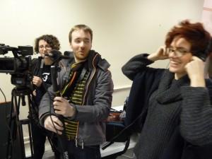Photo of three choir members using camera and headphones