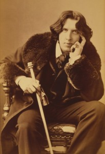 Photo of Oskar Wilde sitting in a chair leaning on his arm and a cane